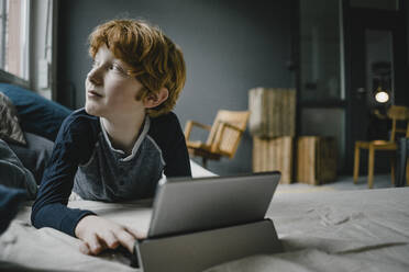 Redheaded boy lying on couch with digital tablet looking out of window - KNSF06242