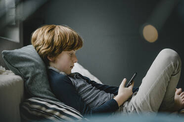 Redheaded boy lying on couch looking at cell phone - KNSF06254