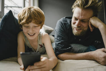 Portrait of happy father and son lying together on couch looking at cell phone - KNSF06266