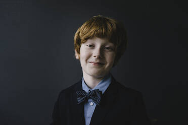 Portrait of smiling redheaded boy wearing bow tie - KNSF06278