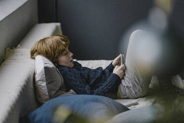 Redheaded boy lying on couch looking at cell phone - KNSF06284