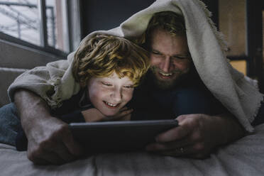 Father and son lying together under blanket looking at digital tablet - KNSF06293