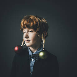 Portrait of redheaded boy wearing bow tie and Christmas baubles - KNSF06302