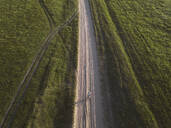 Aerial view of woman with bicycle on dirt road amidst landscape, Tikhvin, Russia - KNTF03037