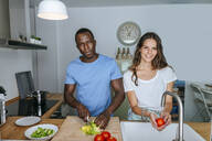Couple preparing salad in kitchen - KIJF02647