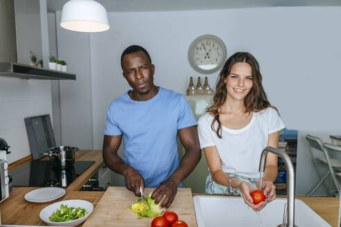 Couple preparing salad in kitchen - KIJF02647