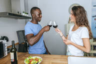 Couple toasting with wine in the kitchen - KIJF02650