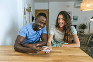 Happy couple using their cell phones at home - KIJF02659