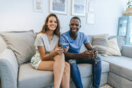 Portrait of smiling couple in living room with cell phones - KIJF02662