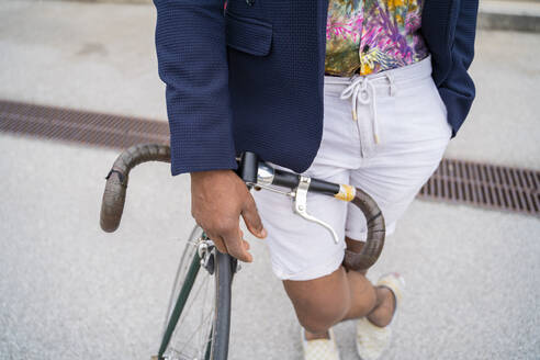 Close-up of stylish man leaning on bicycle - AFVF03843