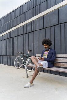 Stylish man using cell phone on a bench - AFVF03852