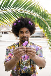 Portrait of man with blossoms in his hair wearing colorful shirt - AFVF03876