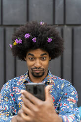 Man with blossoms in his hair wearing colorful shirt taking a selfie - AFVF03879