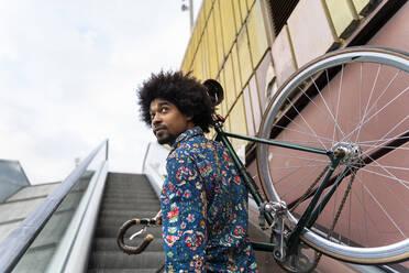 Stylish man carrying bicycle on escalator - AFVF03885