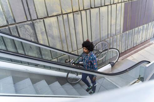 Stylish man carrying bicycle on escalator - AFVF03888