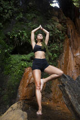 Young woman practising yoga at waterfall, tree position - LJF00714