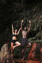 Couple practising yoga at waterfall, tree position - LJF00717