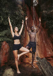 Couple practising yoga at waterfall, tree position - LJF00720