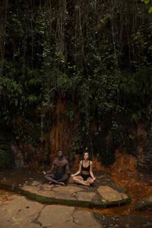 Couple meditating at a waterfall - LJF00723