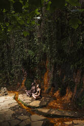 Couple meditating at a waterfall - LJF00726