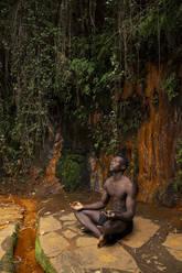 Young man meditating at a waterfall - LJF00729
