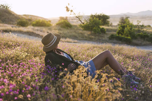 Young woman on meadow at sunset - KNTF03075