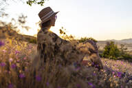 Young woman sitting on meadow at sunset - KNTF03078