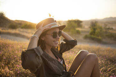 Young woman sitting on meadow at sunset - KNTF03084