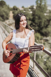 Young woman playing guitar, standing on bridge - LJF00758