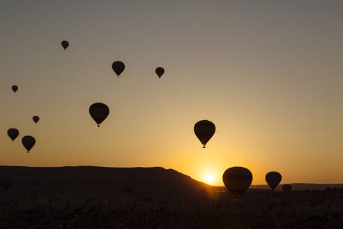 Silhouette hot air balloons flying over landscape during sunset in Goreme, Cappadocia, Turkey - KNTF03091