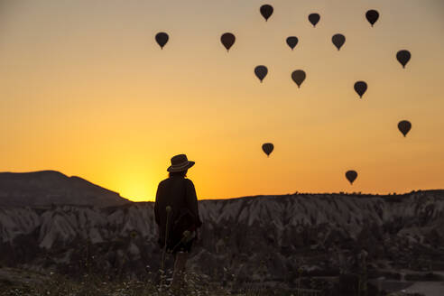Rear view of silhouette young woman looking at hot air balloons while standing on land in Goreme, Cappadocia, Turkey - KNTF03094