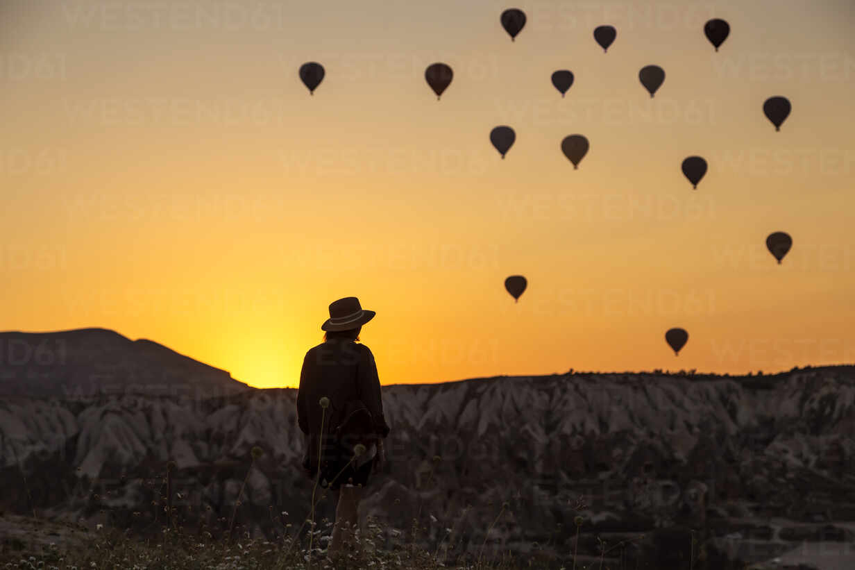 Rear view of silhouette young woman looking at hot air balloons while standing on land in Goreme, Cappadocia, Turkey - KNTF03094 - Konstantin Trubavin/Westend61