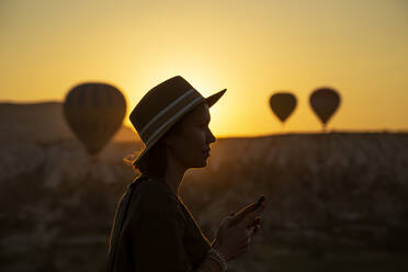 Silhouette young woman using smart phone while standing on land at Cappadocia during sunset, Turkey - KNTF03097