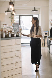 Young woman standing at the counter in a cafe - ALBF00978