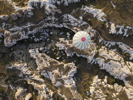 Aerial view of hot air balloon flying over rock formations at Goreme National Park, Cappadocia, Turkey - KNTF03138