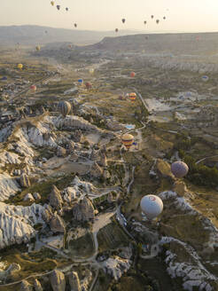 Aerial view of colorful hot air balloons flying over land at Goreme National Park, Cappadocia, Turkey - KNTF03144