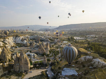 Aerial view of colorful hot air balloons flying over land at Goreme National Park, Cappadocia, Turkey - KNTF03147