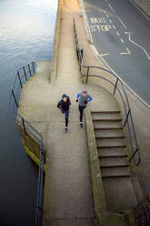 Two teenagers jogging along a river - AJOF00003
