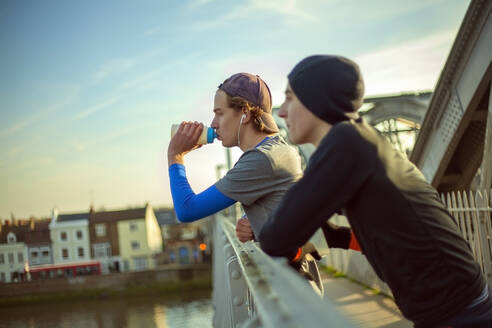 Two young men drinking water after a run by River Thames, London, UK - AJOF00012