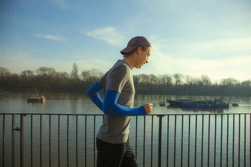 Young man jogging along River Thames, London, UK - AJOF00015
