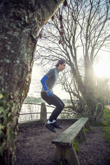 Young sporty man jumping on a wooden bench - AJOF00018