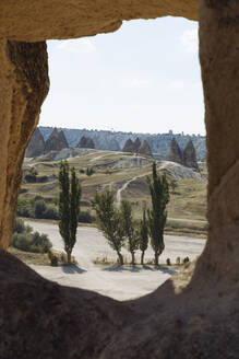 Scenic view of Dove valley against sky seen through cave, Cappadocia, Turkey - KNTF03211