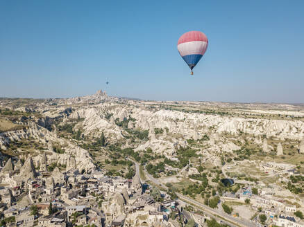Hot air balloon flying over landscape at Goreme National Park, Cappadocia, Turkey - KNTF03214
