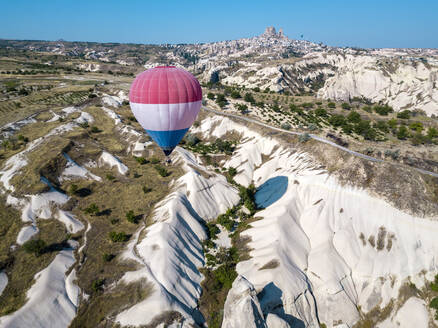 Aerial view of hot air balloon flying over rock formations at Goreme National Park, Cappadocia, Turkey - KNTF03217