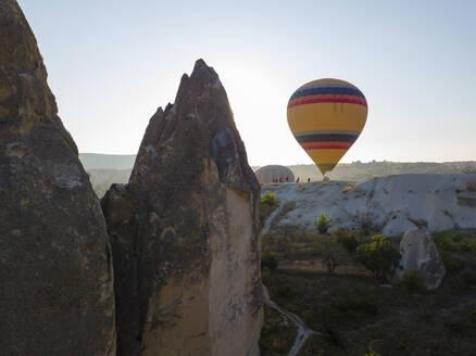 Hot air balloon on mountain against clear sky at Goreme, Cappadocia, Turkey - KNTF03220