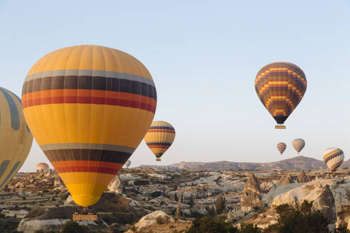 Colorful hot air balloons flying over rocky landscape against clear sky in Cappadocia, Turkey - KNTF03248