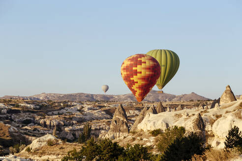 Colorful hot air balloons flying over rocky landscape against clear sky at Cappadocia, Turkey - KNTF03251