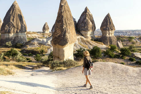 Young woman with backpack walking on land at Goreme village, Cappadocia, Turkey - KNTF03257