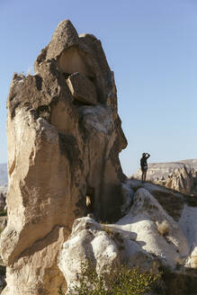 Young woman standing on rock formation against clear blue sky in Goreme, Cappadocia, Turkey - KNTF03266