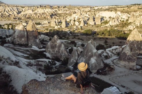 Young woman looking at landscape while sitting on rock in Goreme, Cappadocia, Turkey - KNTF03269